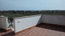 Roof terrace overlooks almond trees and open fields towards the sea