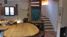 Oak breakfast bar leading to the cosy open plan lounge, log fire and oak spiral staircase