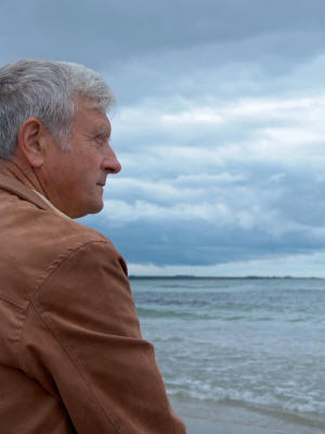 Elderly man looking at the beach